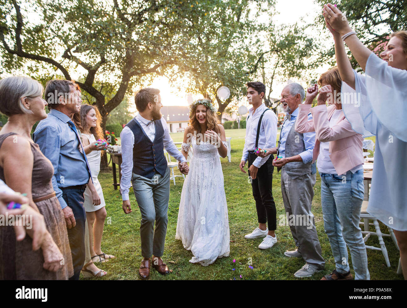 Bride, groom and guests at wedding reception outside in the backyard. - Stock Image