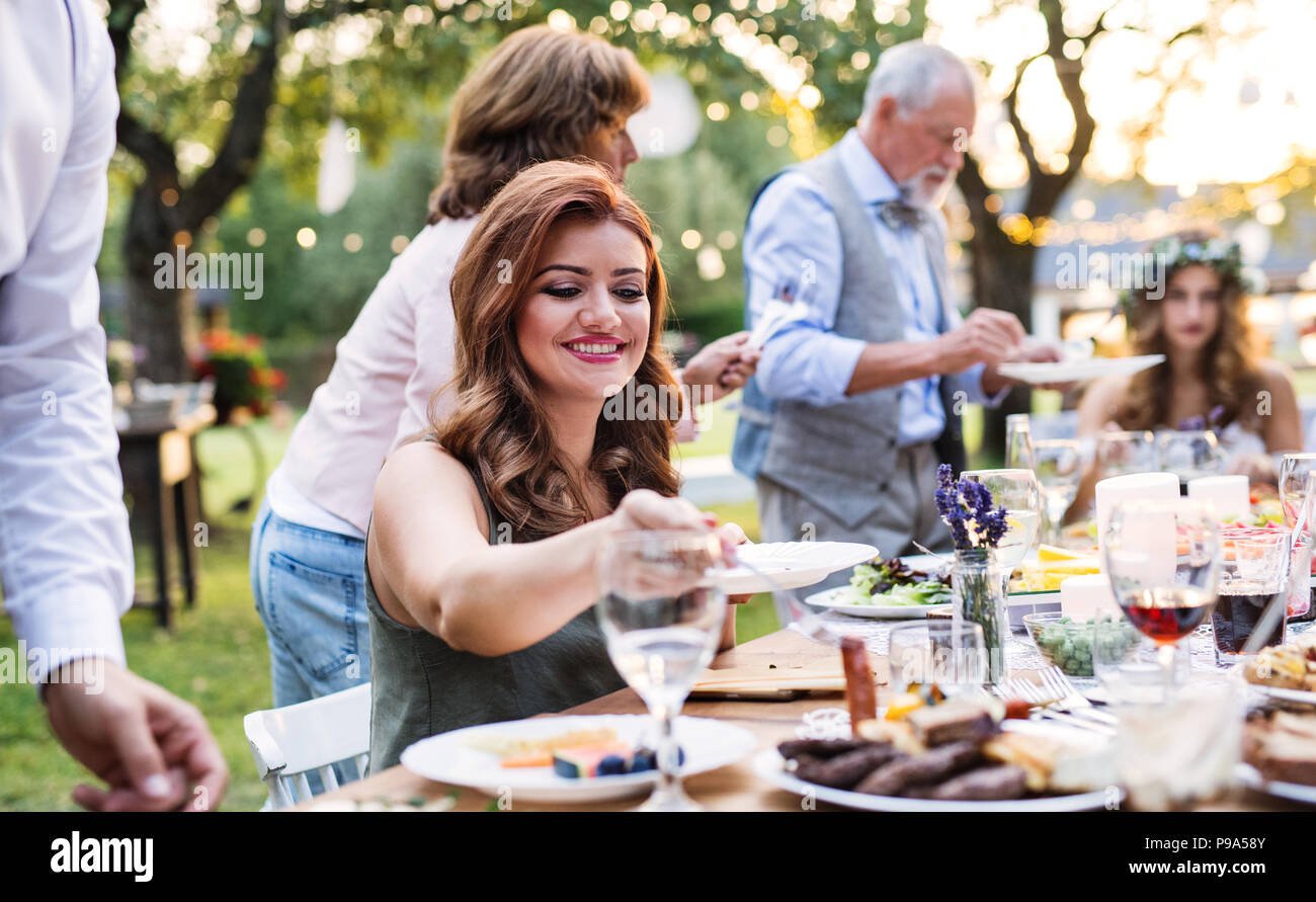 Guests eating at the wedding reception outside in the backyard. - Stock Image