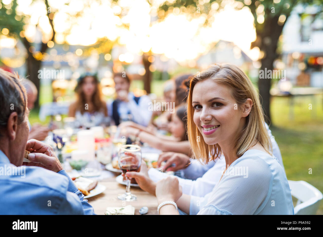 Bride and groom with guests at wedding reception outside in the backyard. - Stock Image