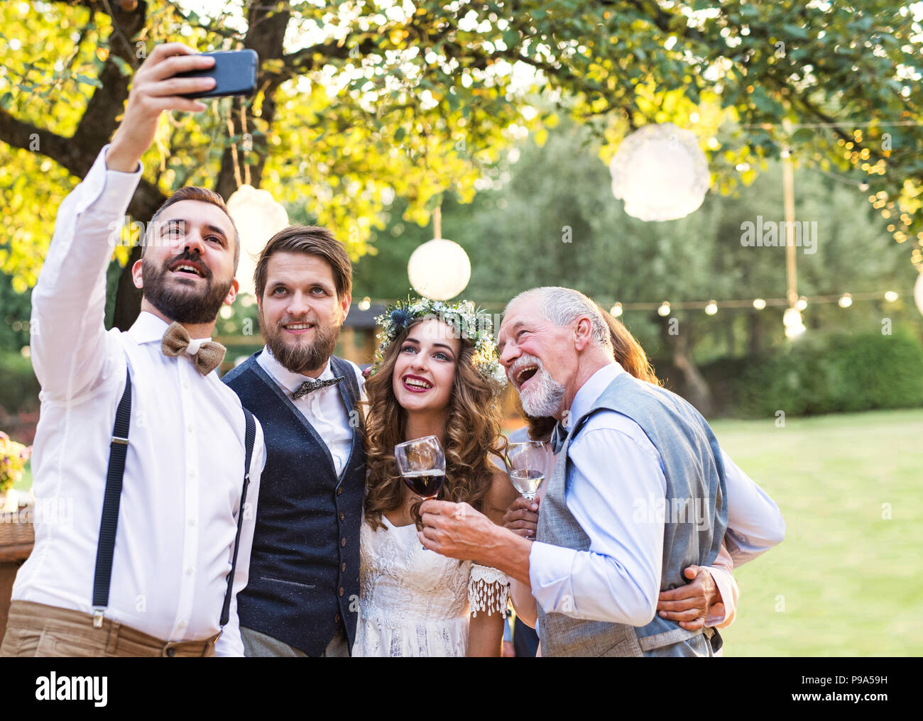 Bride, groom and guests with smartphone taking selfie outside at wedding reception. - Stock Image