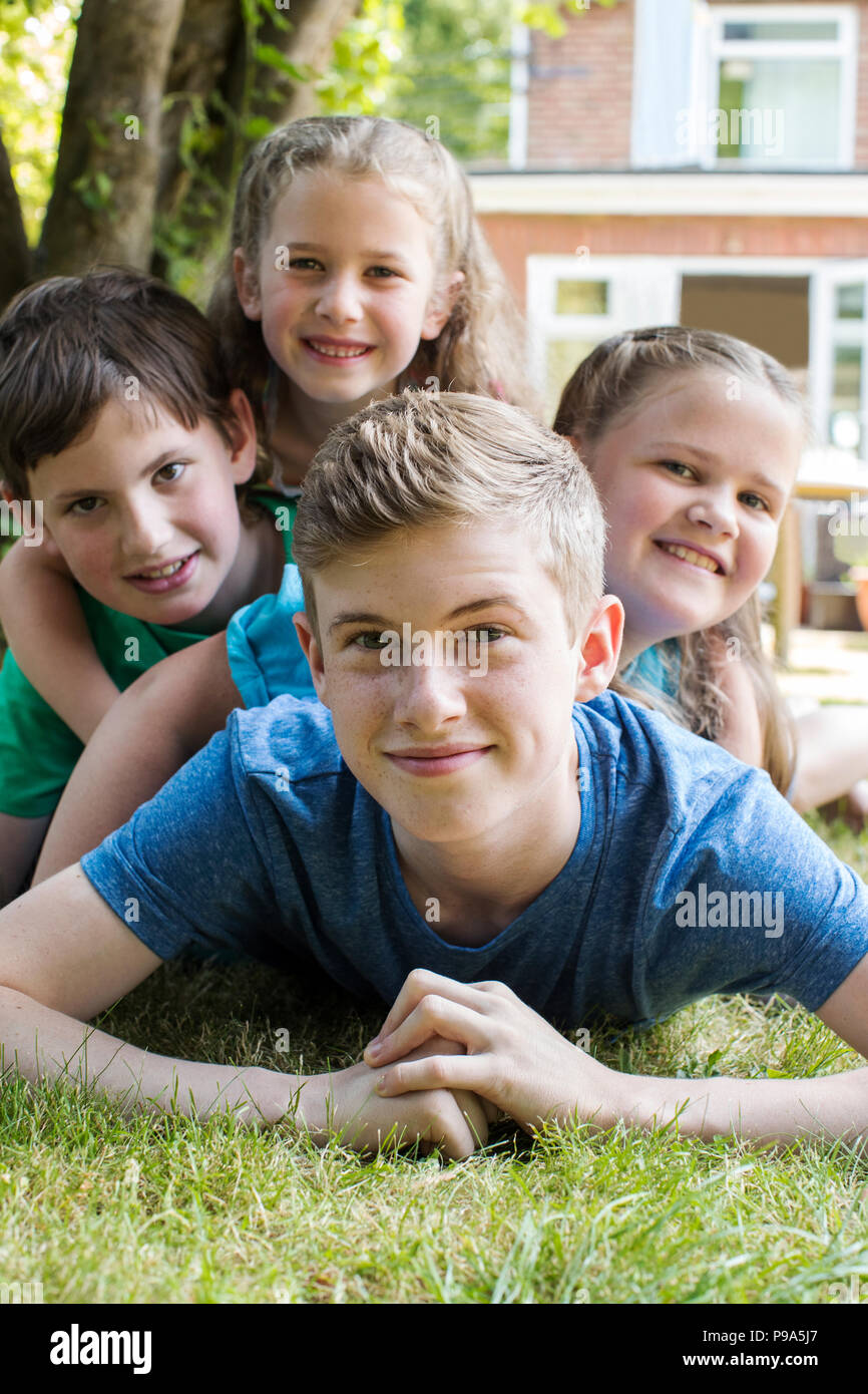 portrait of four brothers and sisters lying in garden at home stock