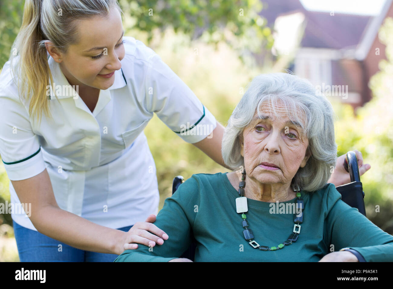 Care Worker Comforting Senior Woman Outdoors In Wheelchair - Stock Image
