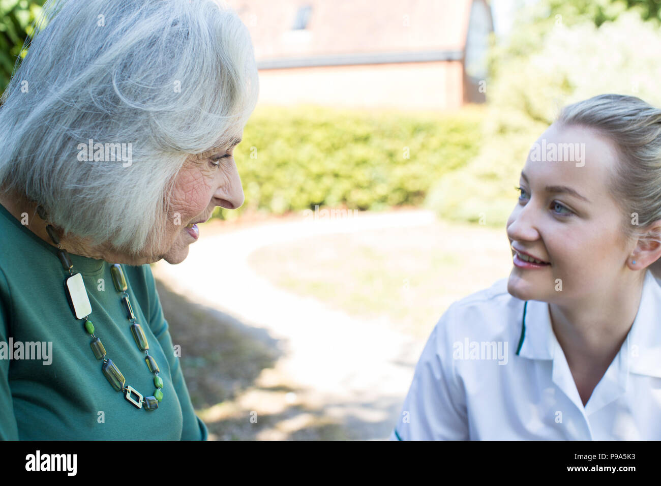 Senior Woman In Garden Talking With Female Carer - Stock Image