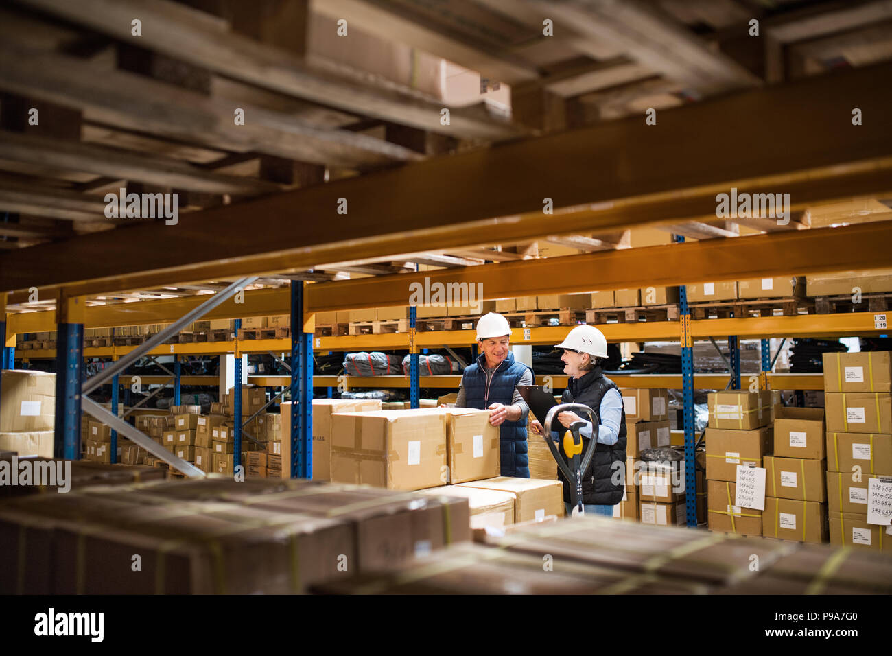 Senior woman and man managers or supervisors working in a warehouse. - Stock Image