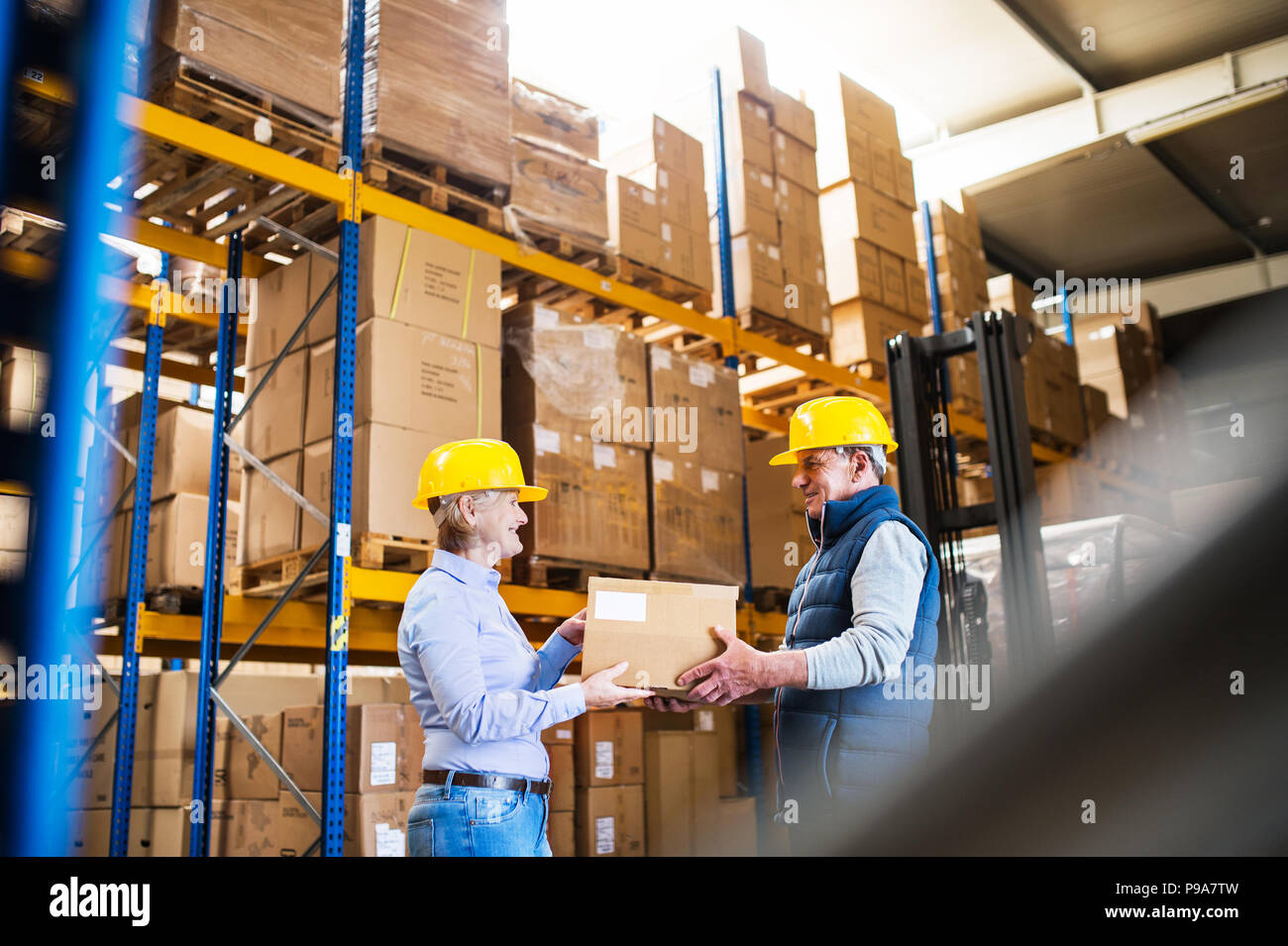 Senior managers or supervisors working together in a warehouse. - Stock Image