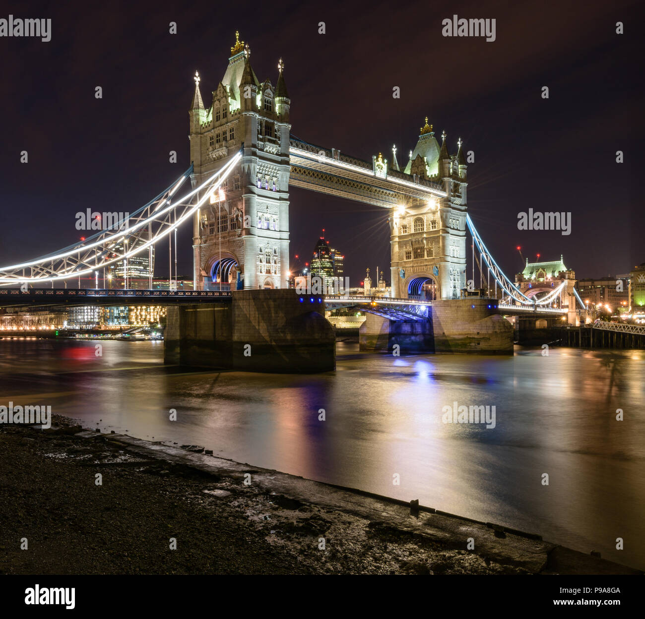 View of Tower Bridge lit up at night from the banks of the River Thames, London, with the Gherkin in the distance - Stock Image