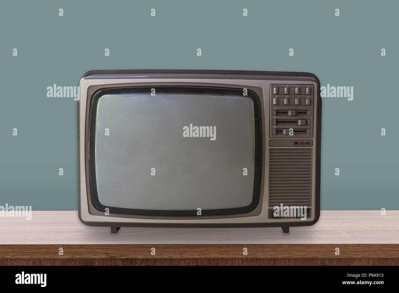 Vintage TV box on wooden table and pastel color background. - Stock Image