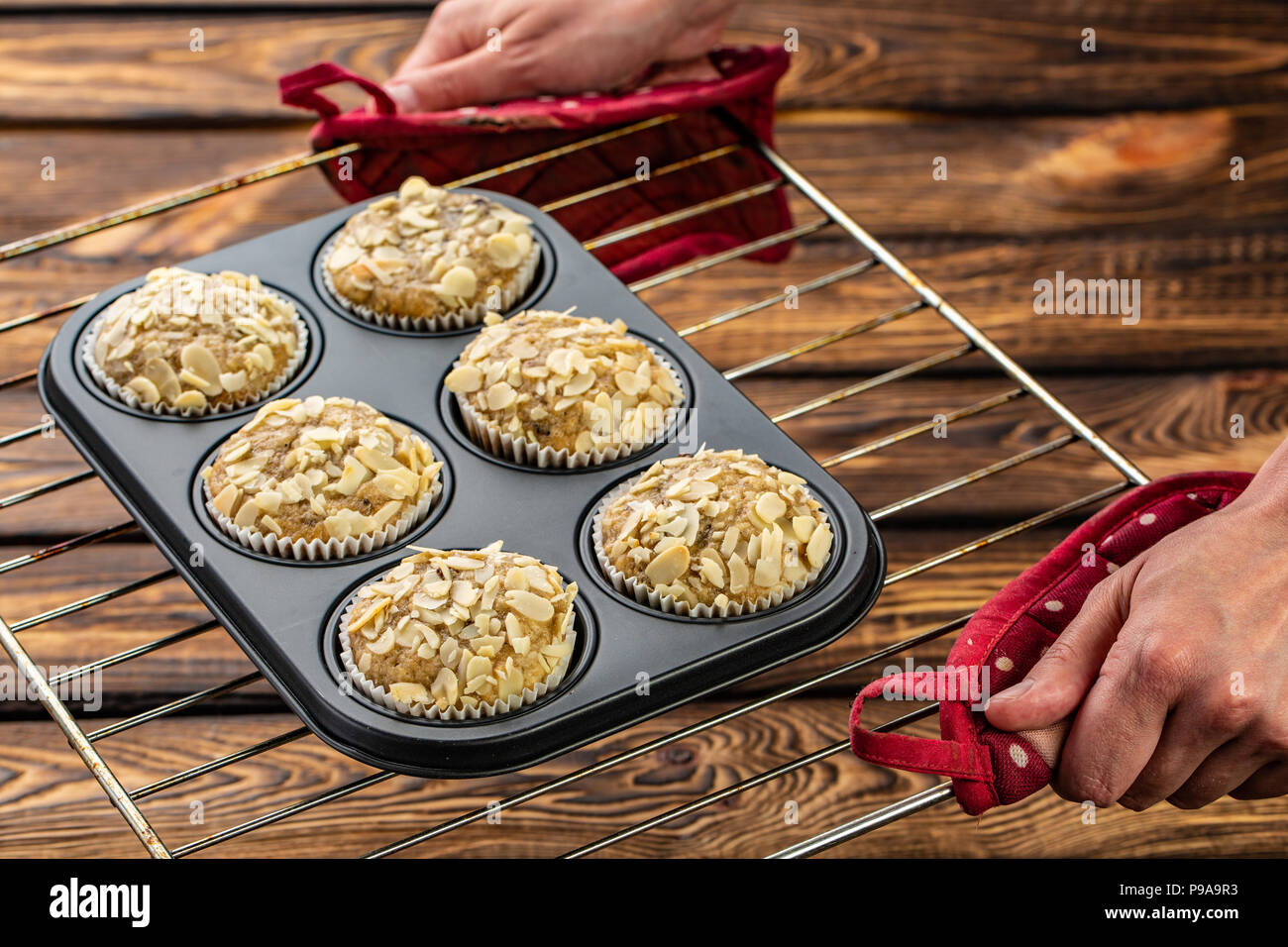 Carrot cupcakes with lemon and apple, almonds on wooden background, raw silicone form on a baking sheet - Stock Image