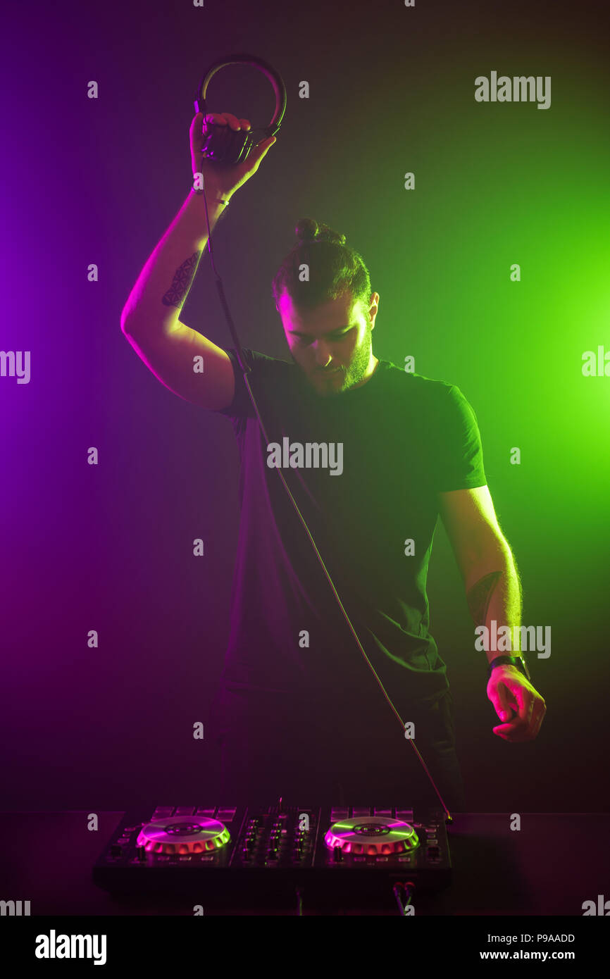 DJ at work mixing sound on her decks at a party or night club with colourful smoke light background - Stock Image