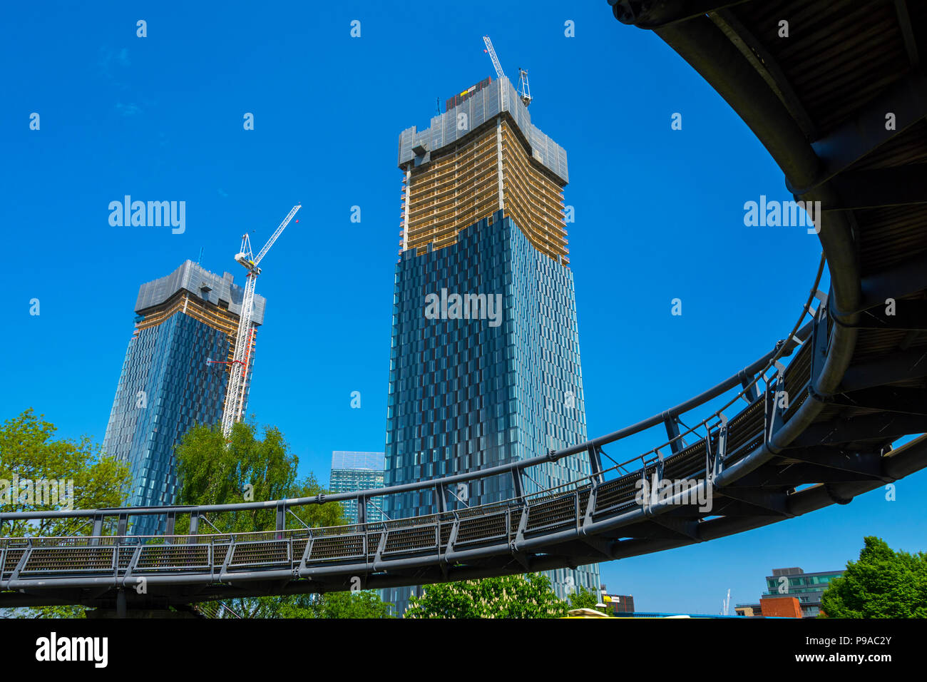 Two of the Deansgate Square apartment blocks (under construction), from the Mancunian Way footbridge, Manchester, England, UK - Stock Image