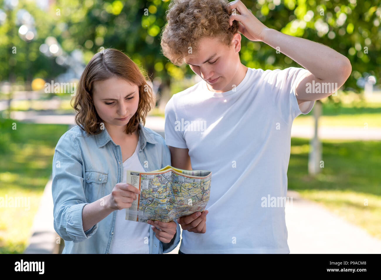 A guy with a girl in summer in the city on nature. In his hands holds a road map. Lost the direction. He does not know where to go. The concept of misunderstanding. He does not know where to go. - Stock Image