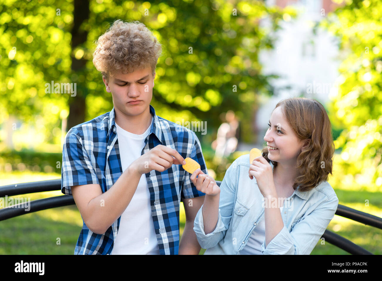 Young students in summer in a park outdoors. They sit on a bench in the city. Girl and happy smiling gives food to guy. The guy is embarrassed. The concept of mistrust. Emotion of kindness. Stock Photo