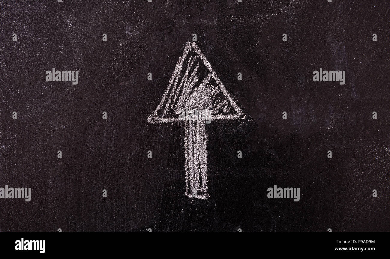 Success concept. Arrow pointing up drawing, isolated, on a blackboard. Stock Photo