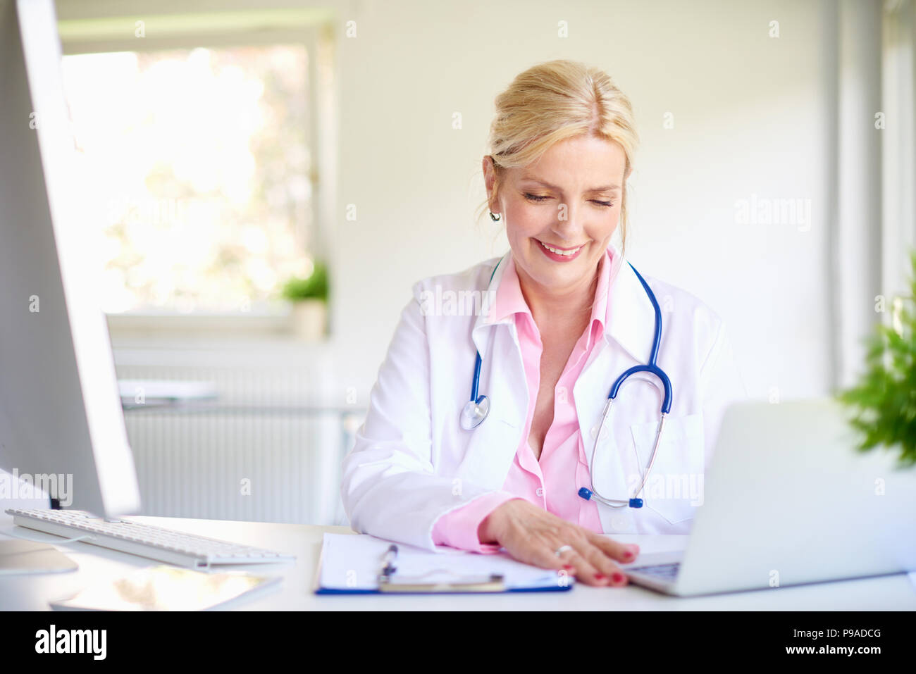 Close-up shot of smiling elderly female doctor using her laptop and writing something while sitting at desk at the doctor's office. - Stock Image