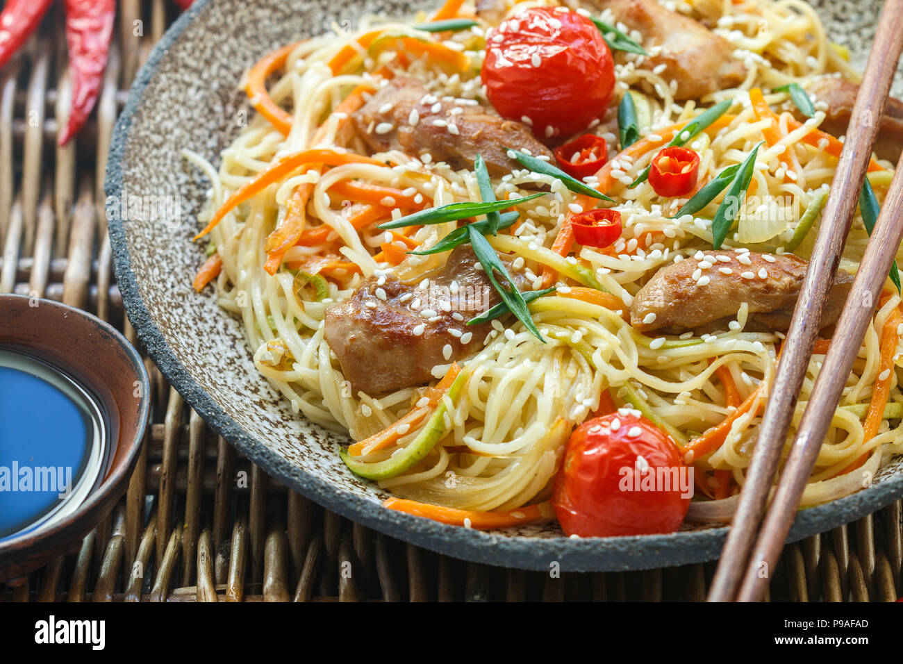 Stir fried noodle with chicken, vegetable (carrot, tomato,  zucchini, garlic, red pepper, green onion), sesame seeds and soy sauce on clay plate close - Stock Image