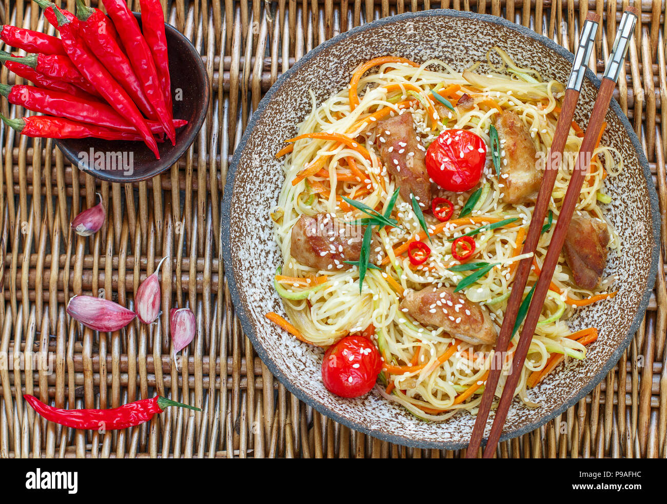 Stir fried noodle with chicken, vegetable (carrot, tomato, zucchini, garlic, red pepper, green onion), sesame seeds and soy sauce on clay plate. Asian - Stock Image
