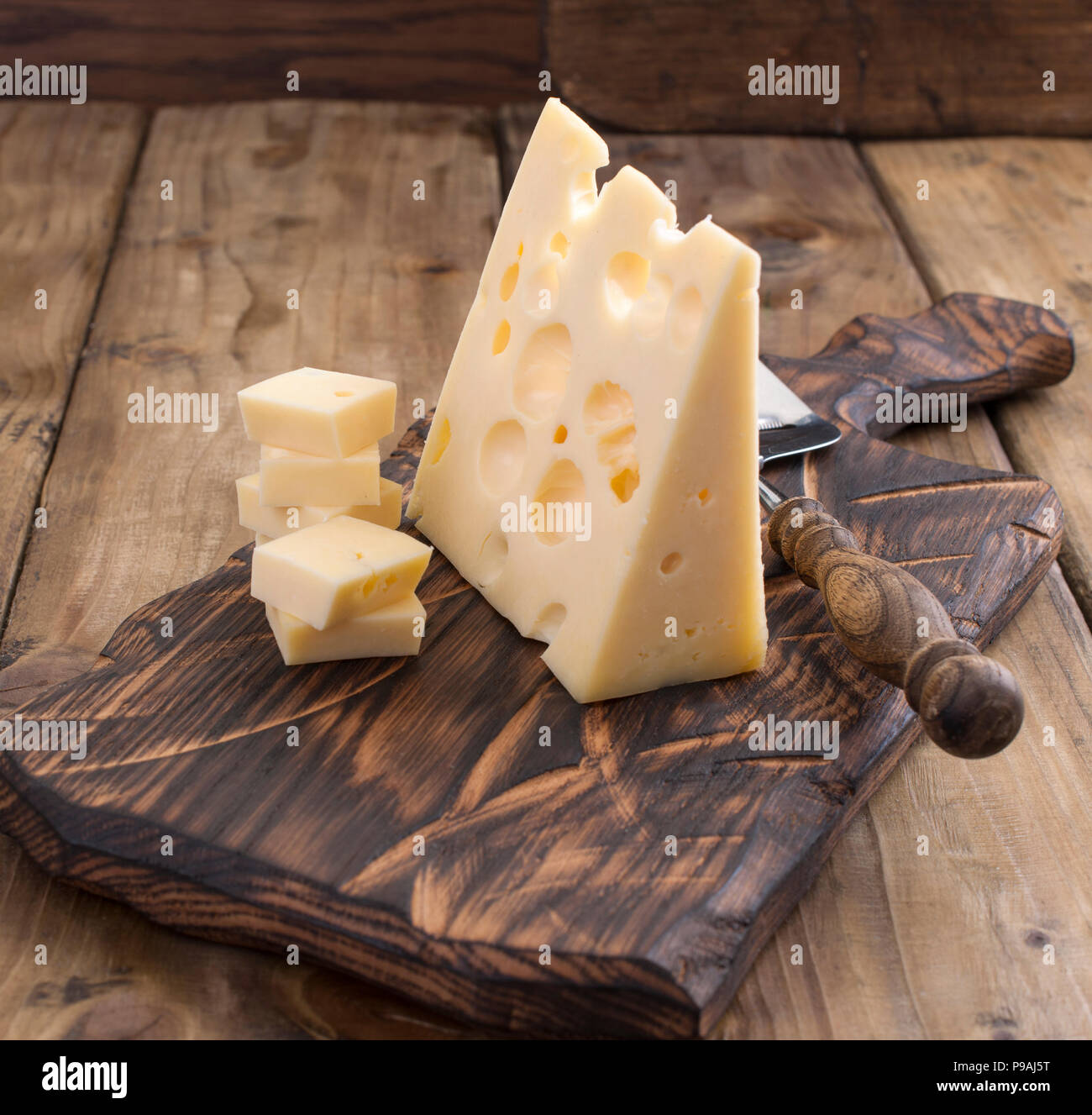 Dutch cheese with holes on a wooden old board and cheese knead. Vintage photo. Dairy. Free space for text. Copy space Stock Photo