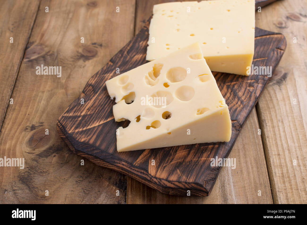 Dutch cheese with holes on a wooden old board. Vintage photo. Dairy. Free space for text. Copy space - Stock Image
