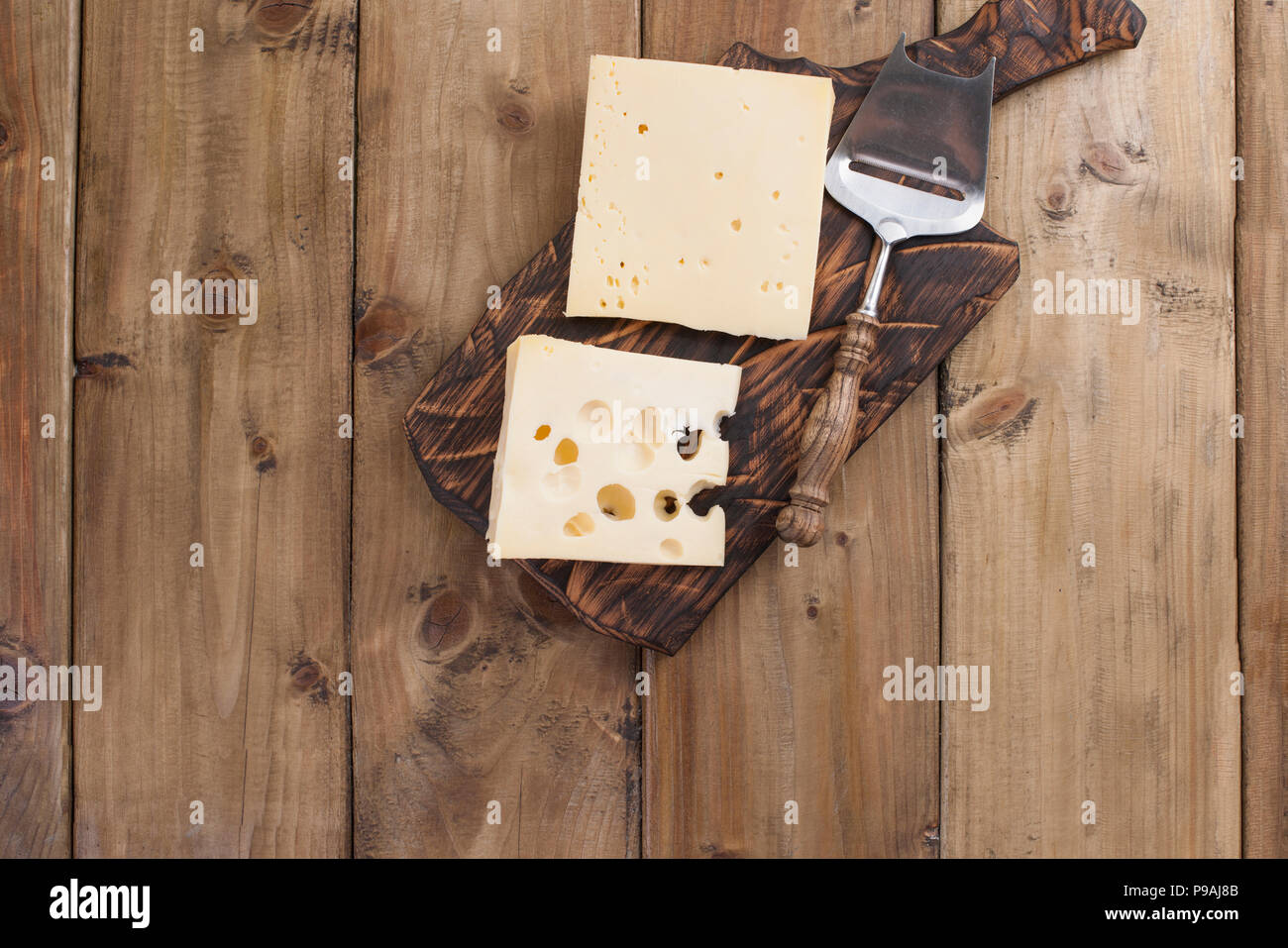 Dutch cheese with holes on a wooden old board and cheese knead. Vintage photo. Dairy. Free space for text. Copy space - Stock Image