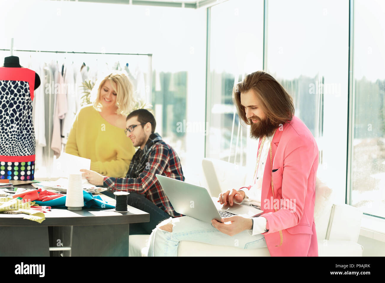 fashion designer working on a laptop in a creative office - Stock Image