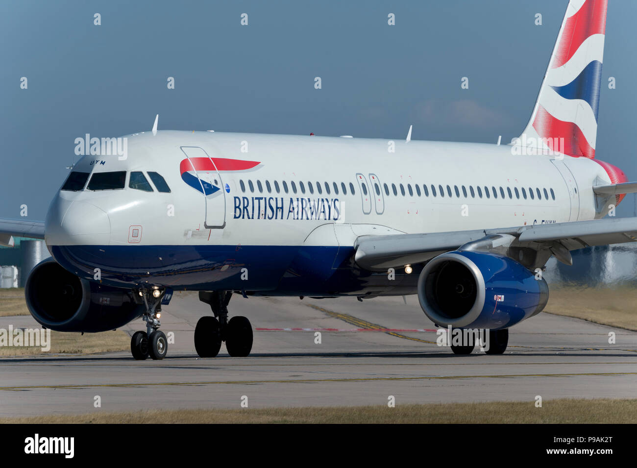 A British Airways Airbus A320-232 taxis along the runway at Manchester Airport whilst preparing to take off. - Stock Image