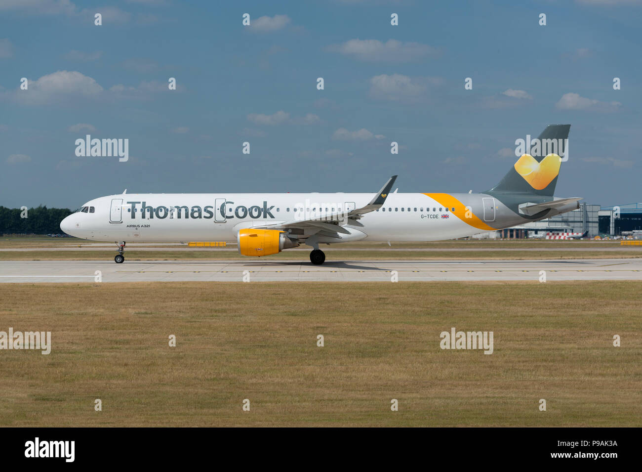 A Thomas Cook Airbus A321-211 sits on the runway at Manchester Airport as it prepares to take-off. - Stock Image