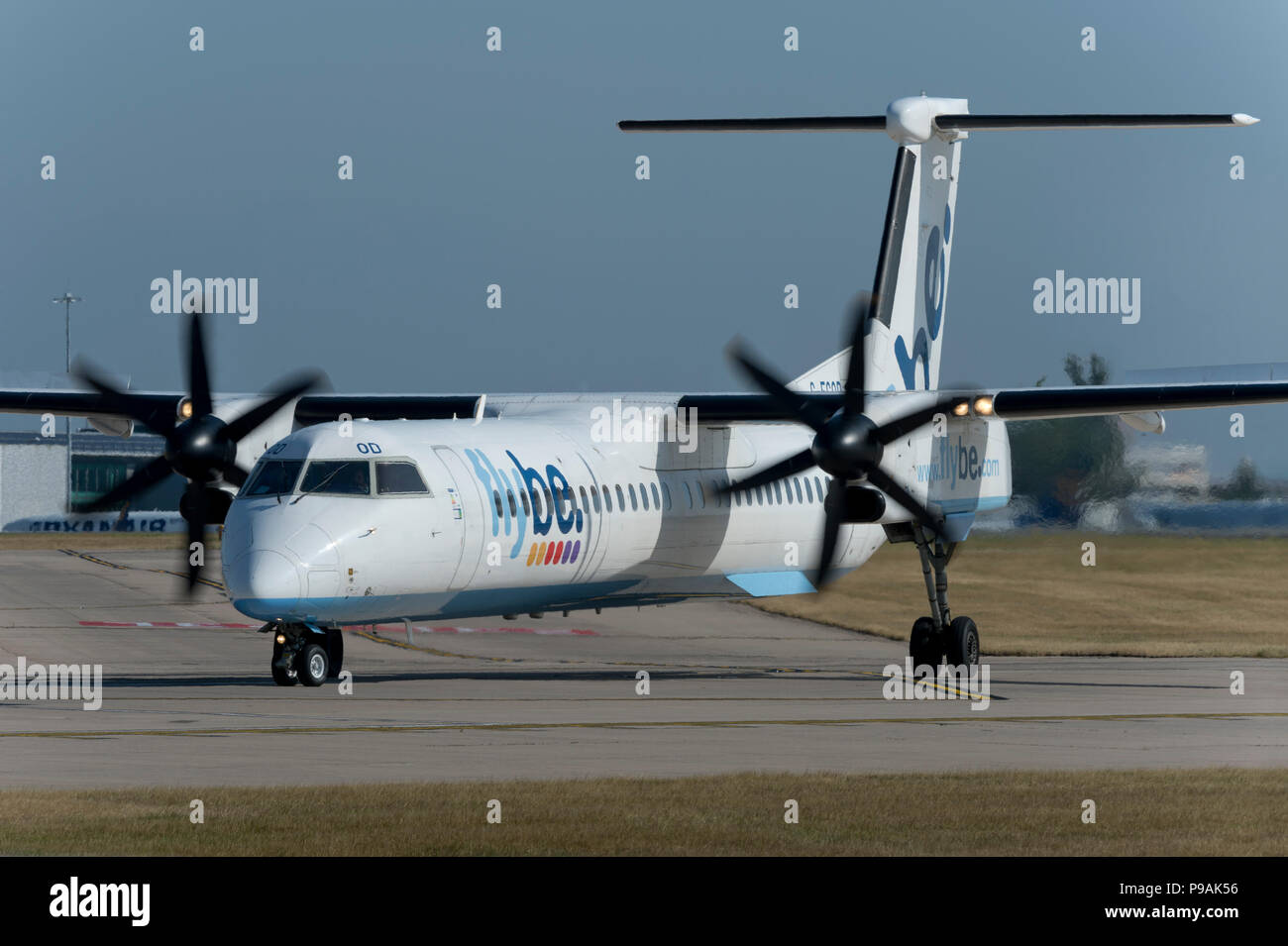 A Flybe Bombardier Dash 8 Q400 taxis along the runway at Manchester Airport whilst preparing to take off. - Stock Image