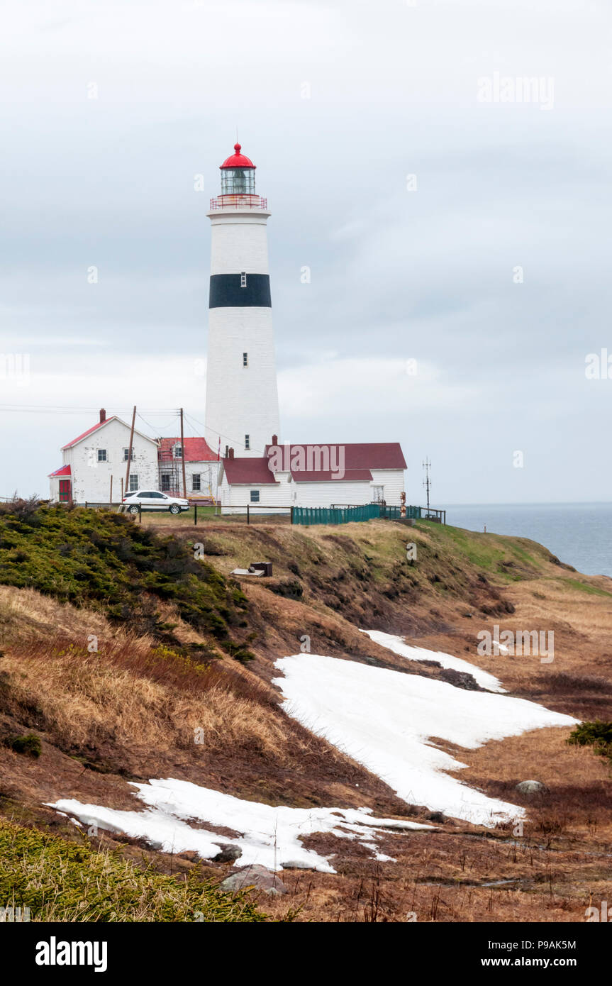 Remains of drifted snow in front of Point Amour Lighthouse in Labrador, Canada. - Stock Image