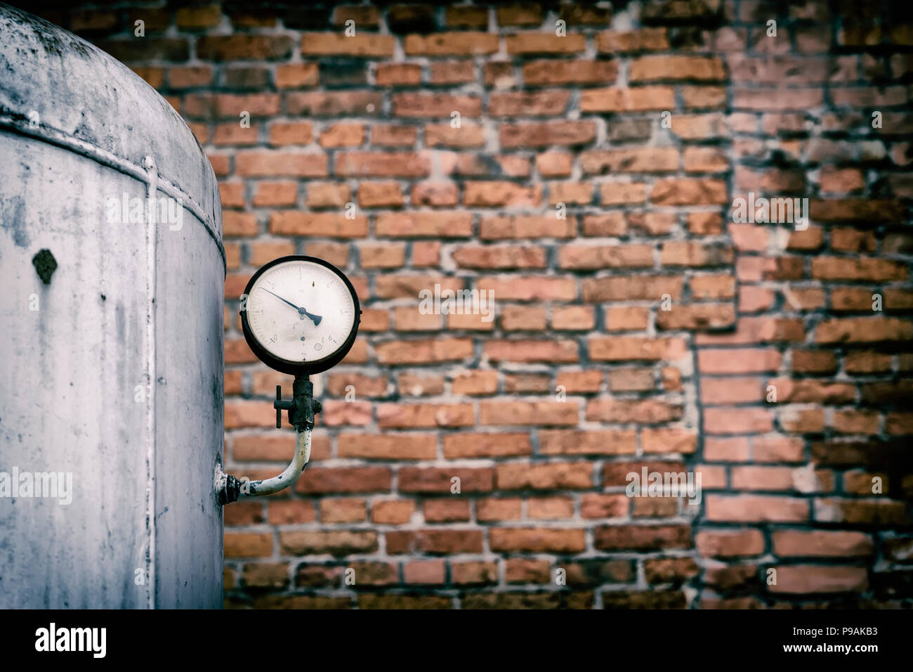 Old pressure gauge of the tank against the backdrop of a brick wall. Pressure sensor - Stock Image