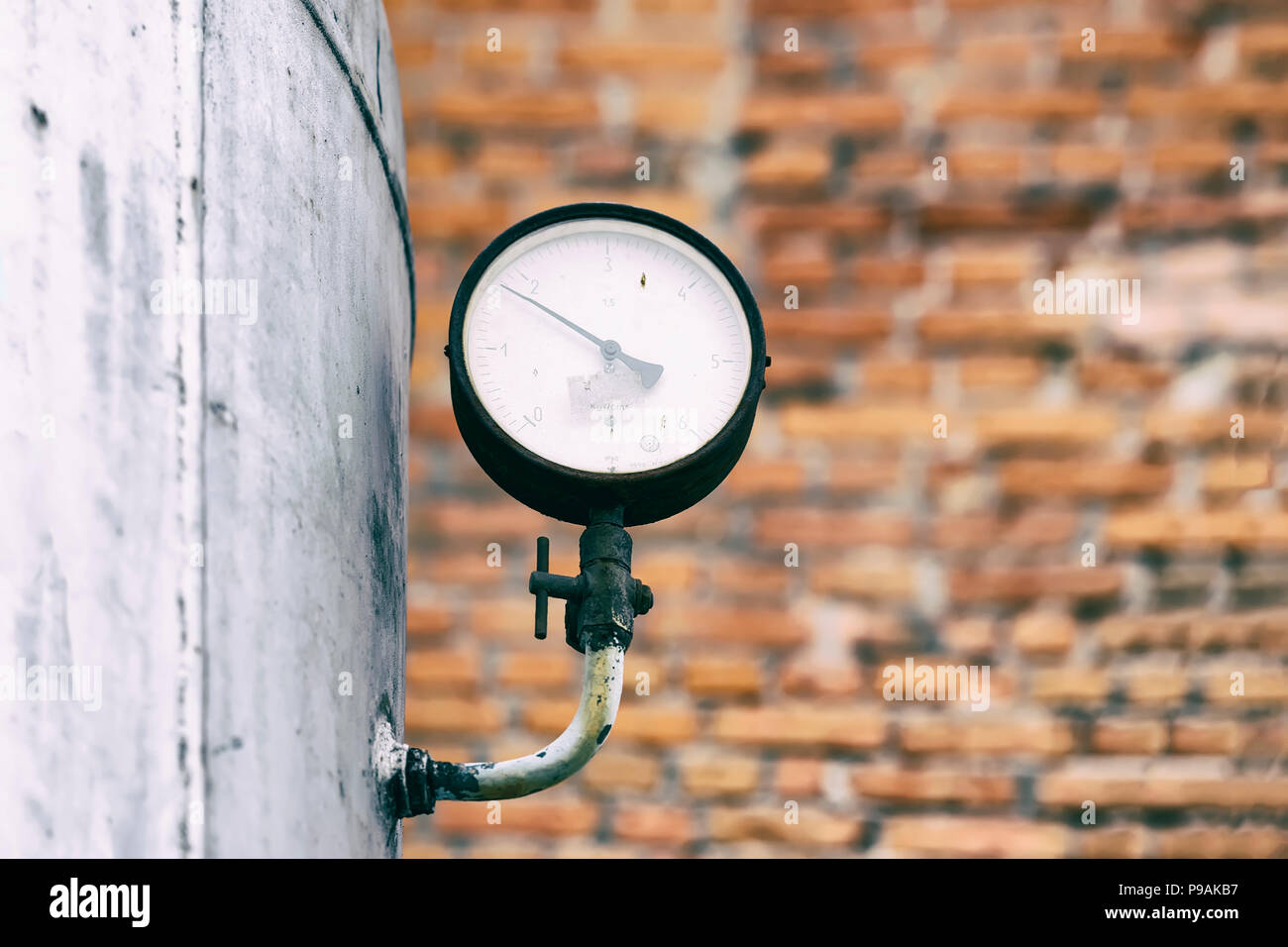 Old pressure gauge of the tank. Pressure sensor against a brick wall background - Stock Image