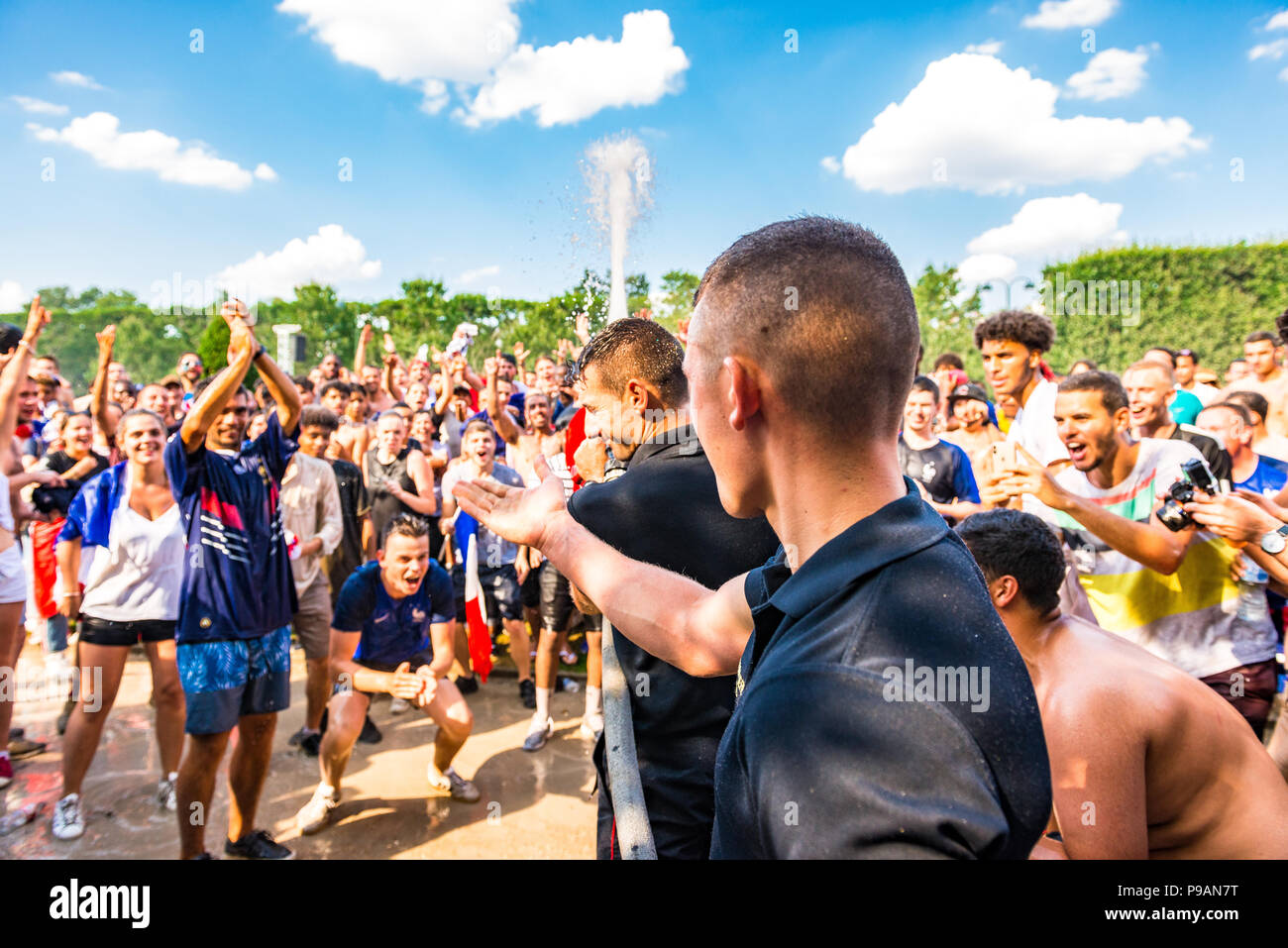 Firemen hose the crowd with water on the Champ de Mars in Paris as France wins the World Cup. Paris, France. - Stock Image