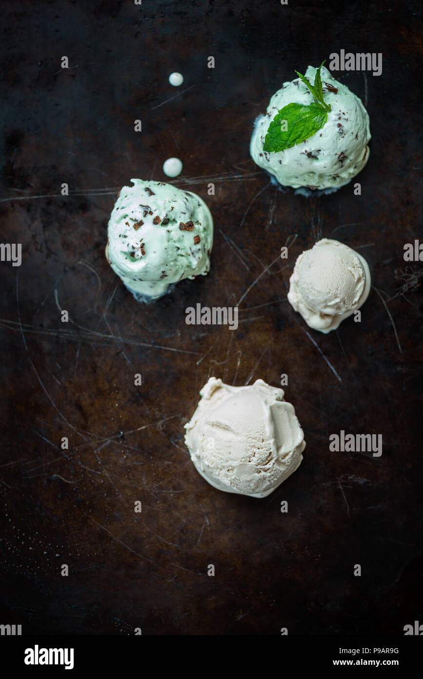 Selection of different ice cream scoops such as mint, chocolate and strawberry on dark background, top view Stock Photo