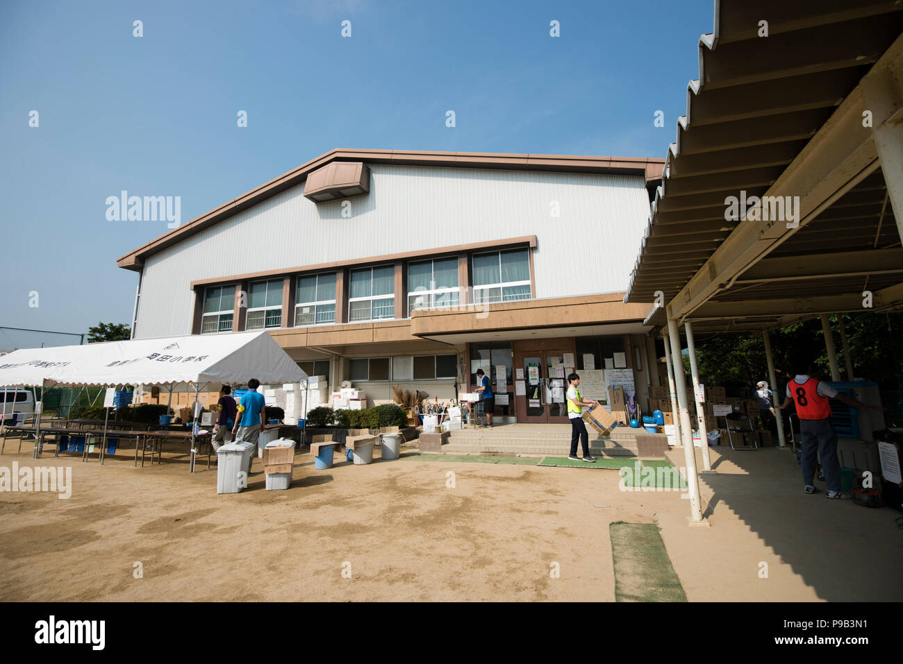 Okayama, Japan. 17th July 2018. Volunteers work outside the gymnasium at Okada Elementary School, a temporary shelter for flood victims in Mabicho, Kurashiki, Okayama Prefecture, Japan. More than 200 people died in floods and landslides caused by torrential rains more than a week ago. On Sunday, the government announced the weather event would be designated an extremely severe disaster, freeing up recovery funds for the affected areas. Cleanup and recovery efforts have been hampered by extreme heat. Credit: Aflo Co. Ltd./Alamy Live News - Stock Image