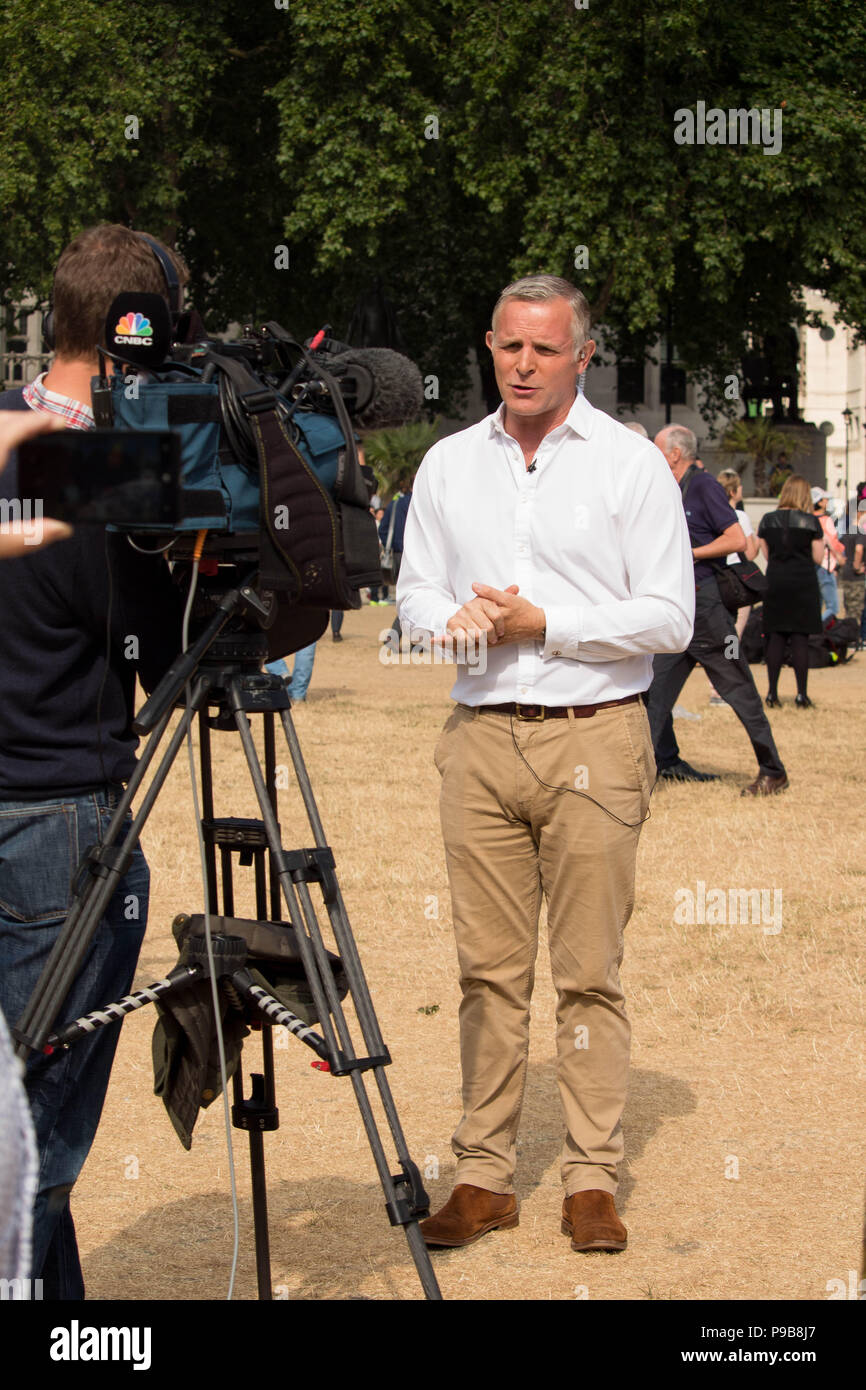News reporter presenting coverage of 'STOP TRUMP' protest march in Parliament Square Gardens, London, UK 13/7/18. - Stock Image