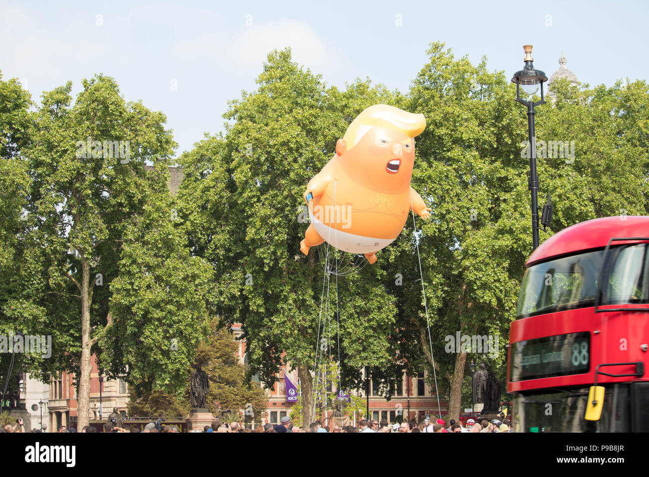 STOP TRUMP' protests in Parliament Square Gardens-  'Trump Baby' giant inflatable rises up above the crowds as Red London bus travels by.London, UK. - Stock Image