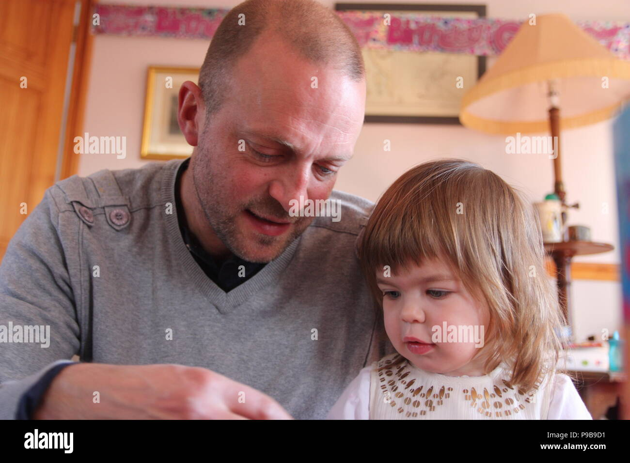 Man and young girl bonding in sweet picture in sitting room at home - Stock Image