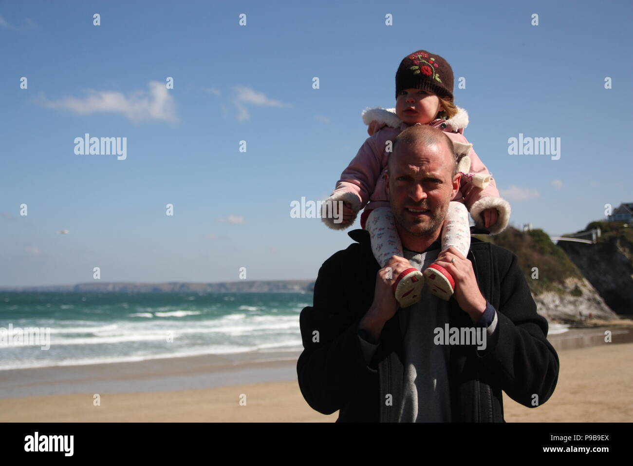 Man with young girl on his shoulder on a sandy beach at seaside Marazion Cornwall - Stock Image