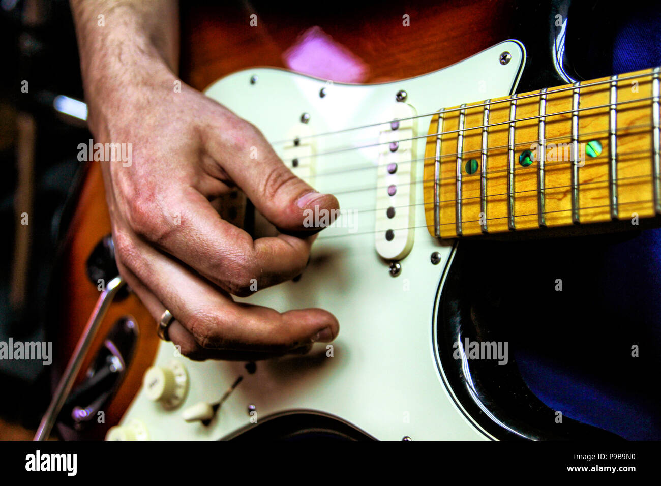 Young man playing electric guitar. Focus on the hand - Stock Image
