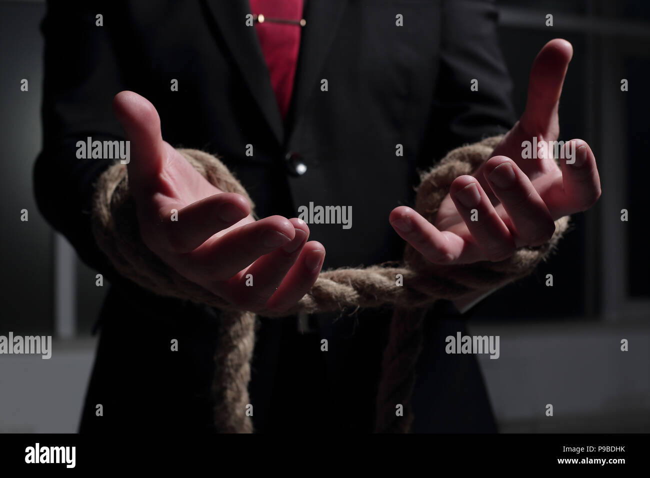 Businessman with hands tied in ropes. - Stock Image