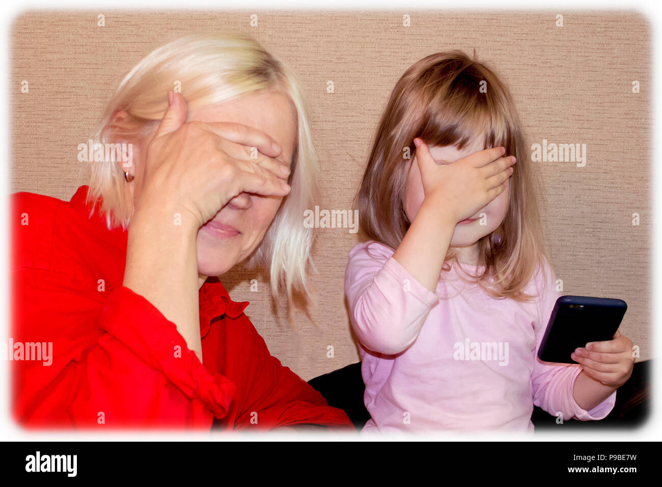 Beautiful young blonde grandmother and little cute granddaughter closing eyes with hands - Stock Image
