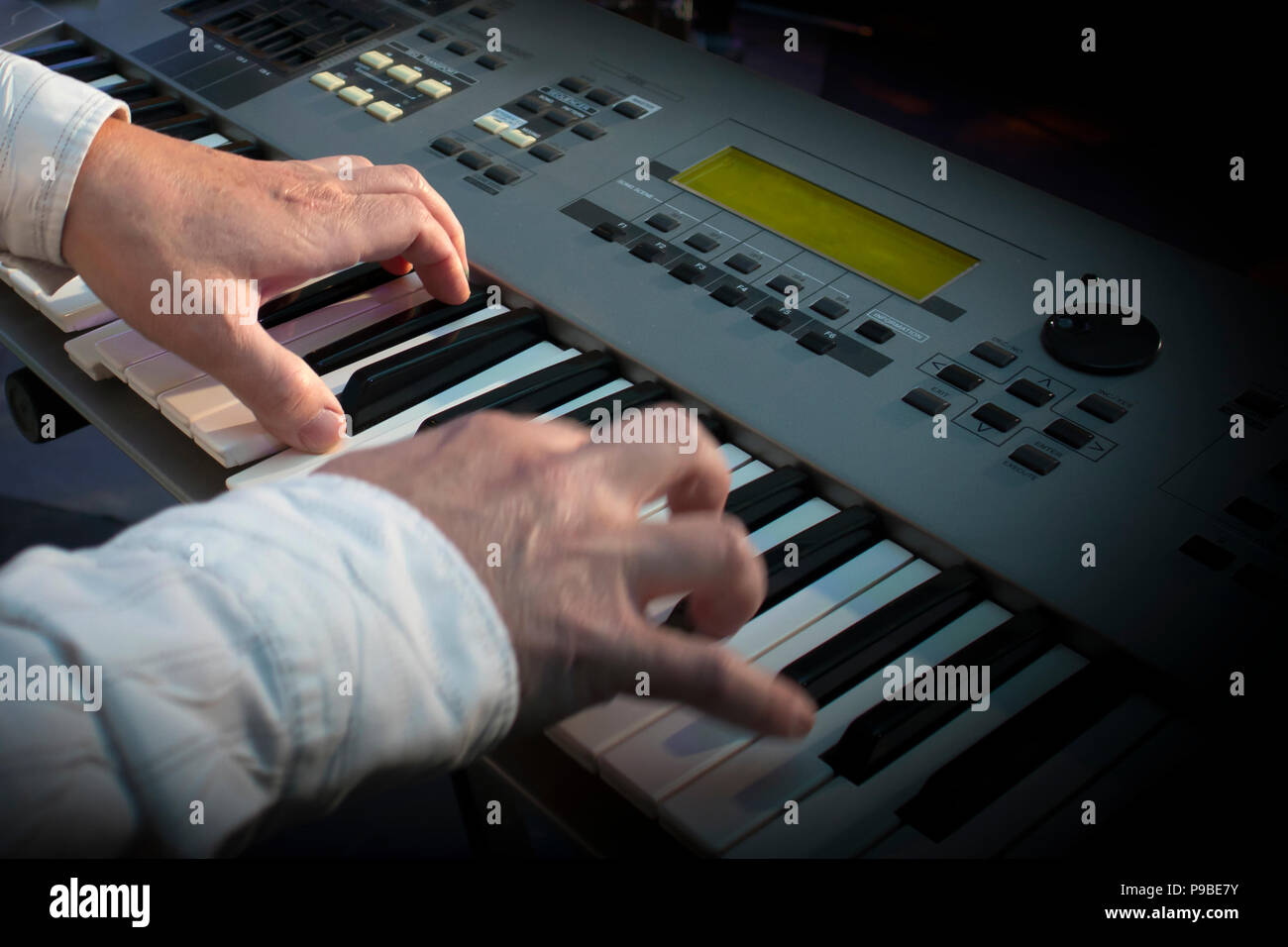 Closeup hands of musician playing synthesizer in concert - Stock Image
