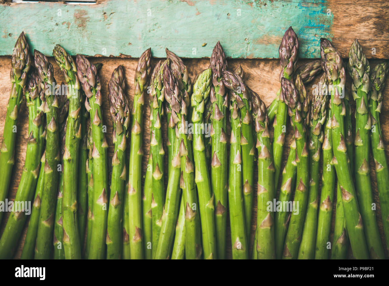Raw uncooked green asparagus over rustic wooden tray background, close-up - Stock Image