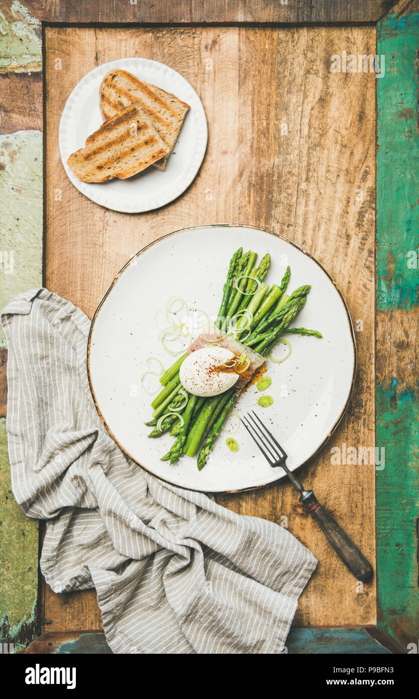 Flat-lay of green asparagus, soft-boiled egg , bacon, leek and toasts - Stock Image