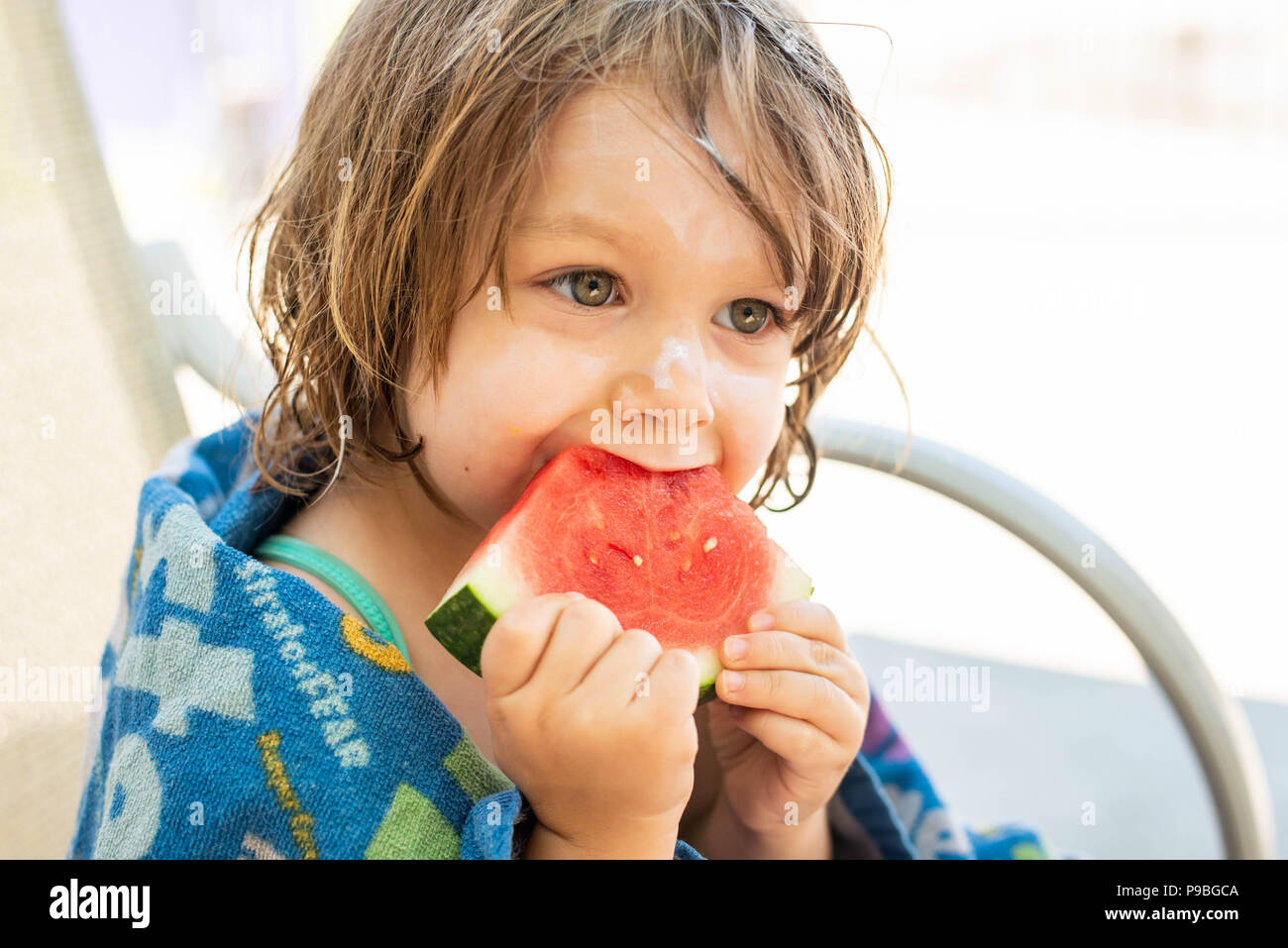 A young girl with sunblock on her head eats watermelon at a waterpark in Pennsylvania, United States. - Stock Image
