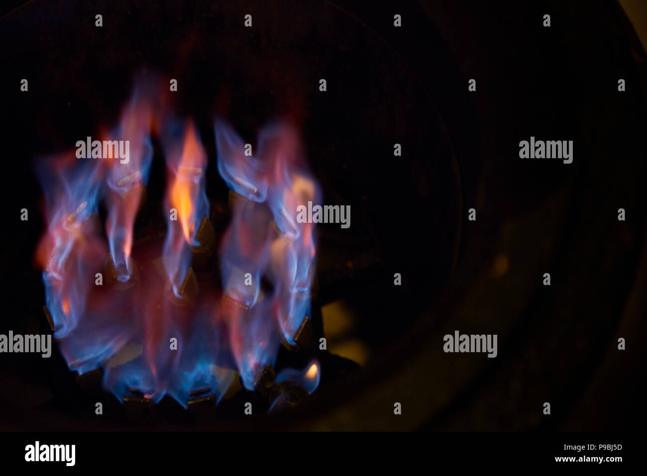 Gas burner lit with fire on an industrial stove top. - Stock Image