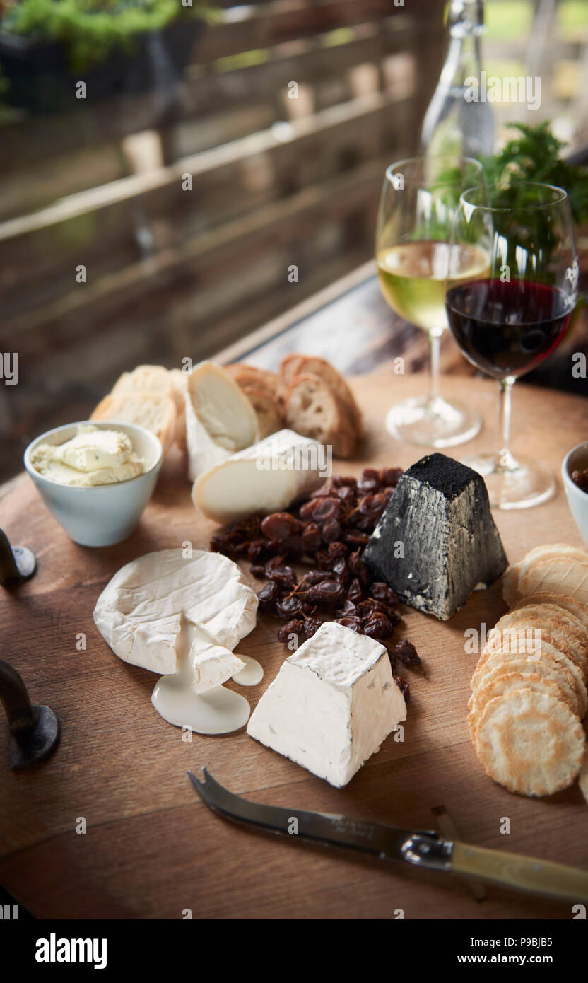 Generous heaving cheese and cracker board with wine. - Stock Image