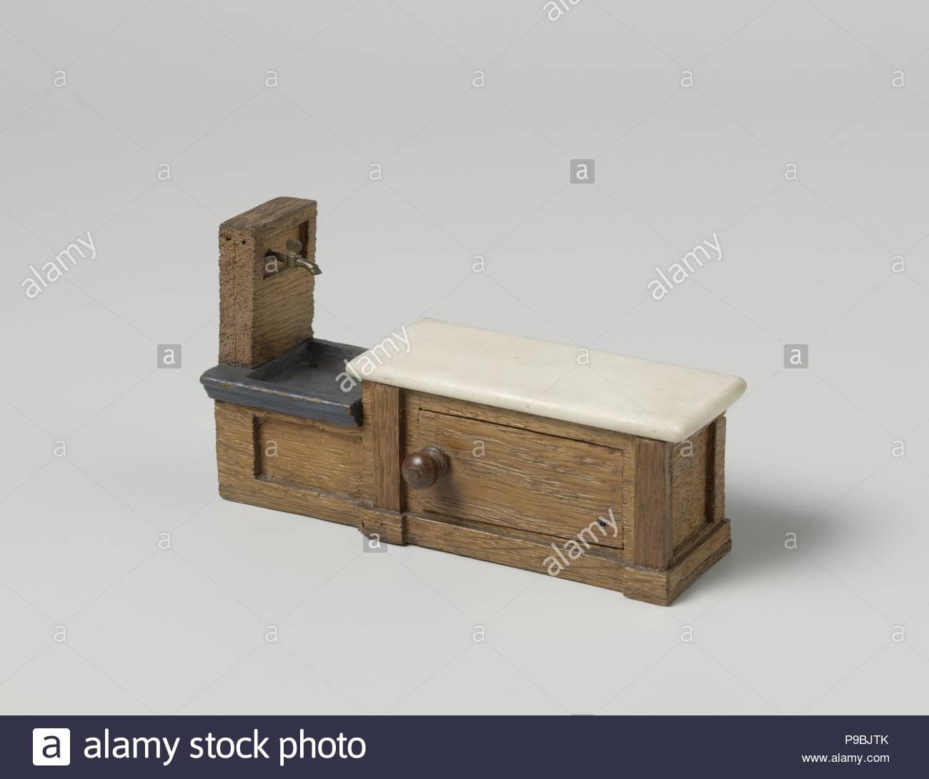 An oak fountain or pump sink cupboard, reservoir with two brass ...