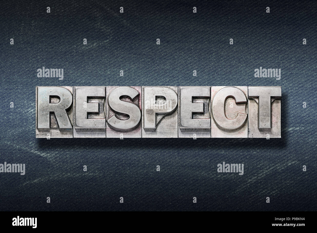 respect word made from metallic letterpress on dark jeans background - Stock Image