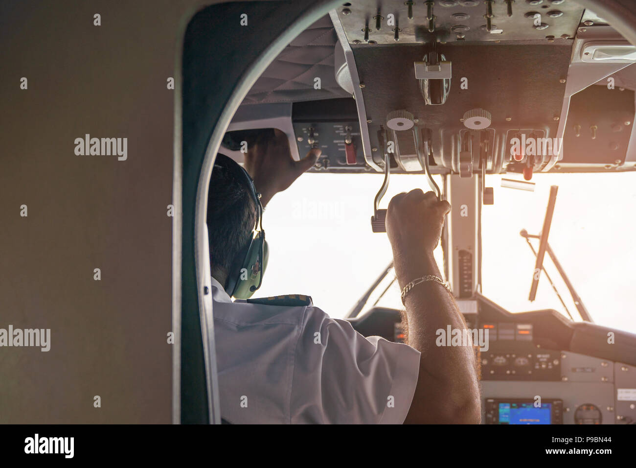 Interior details of airplane with pilot on board while flying, on white sky background. - Stock Image