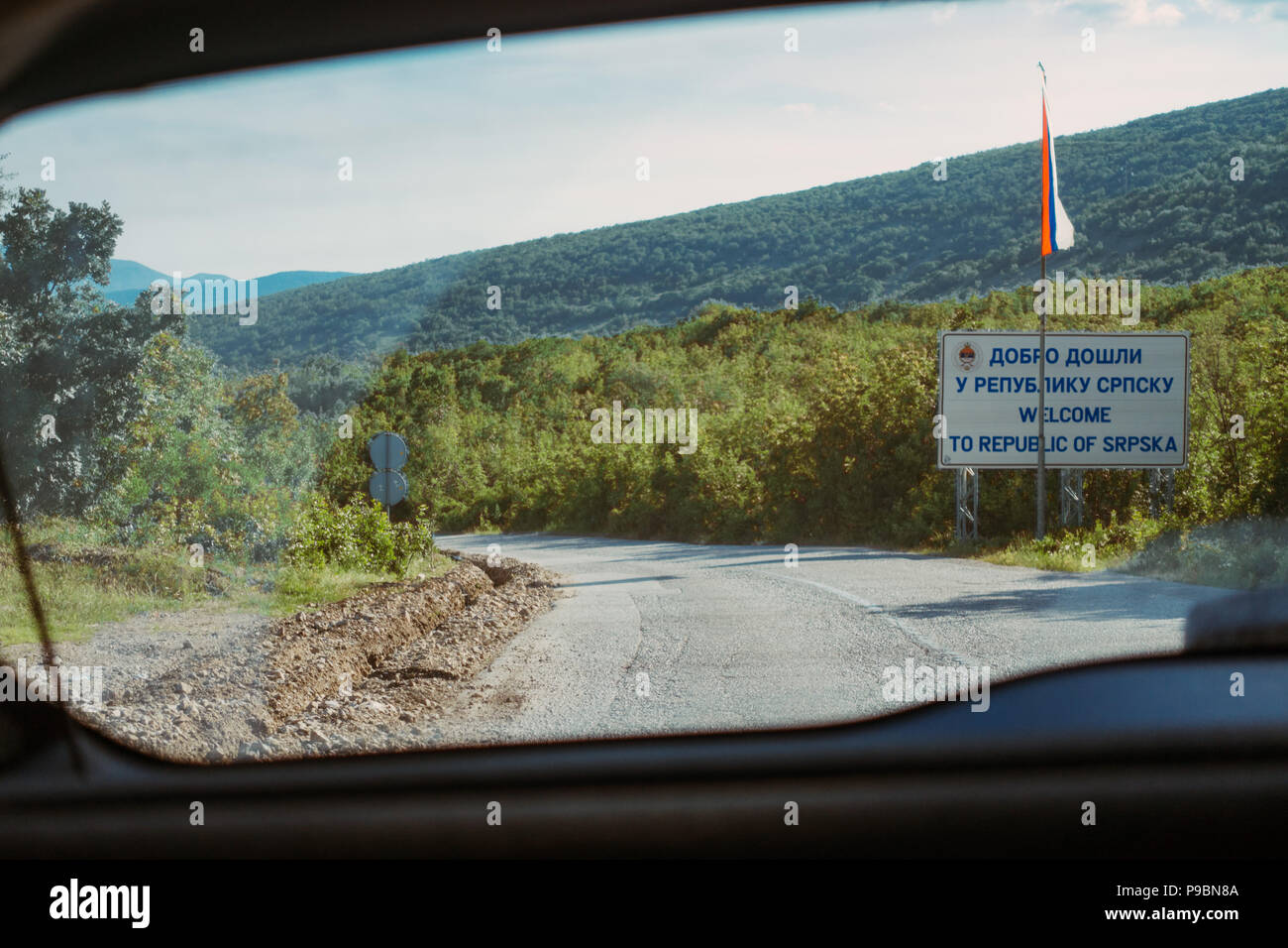 The view out the rear window of a car crossing the border leaving Republic of Srpska, Bosnia and Herzegovina - Stock Image